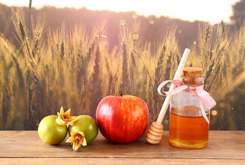 Rosh-hashanah (jewesh Feiertag) Konzept - Honig, Apfel und Granatapfel über Holztisch traditionelle Feiertagssymbole stockbild