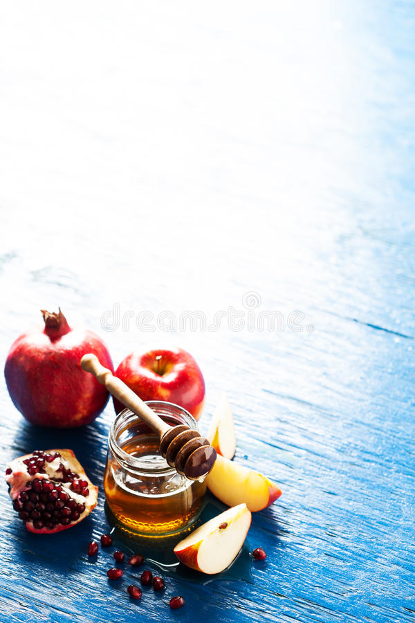 Rosh hashanah. Jewesh holiday concept: honey, apple and pomegranate, with space for text royalty free stock image
