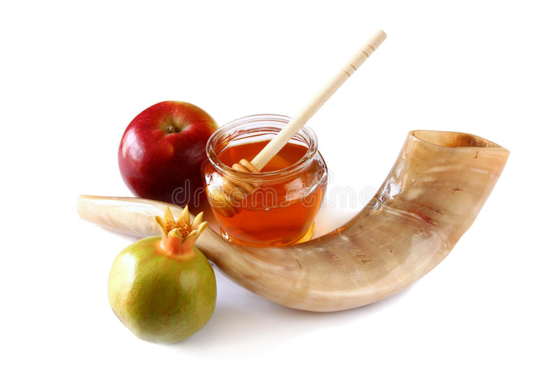 Rosh hashanah (jewesh holiday) concept - shofar (horn), honey, apple and pomegranate isolated on white. traditional holiday symbol royalty free stock images