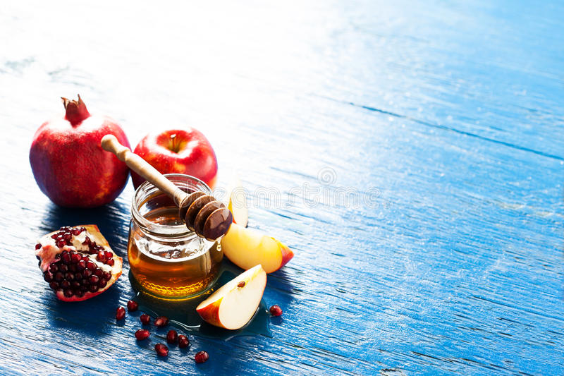 Rosh hashanah. (jewish holiday) concept: honey, apple and pomegranate, with space for text royalty free stock images