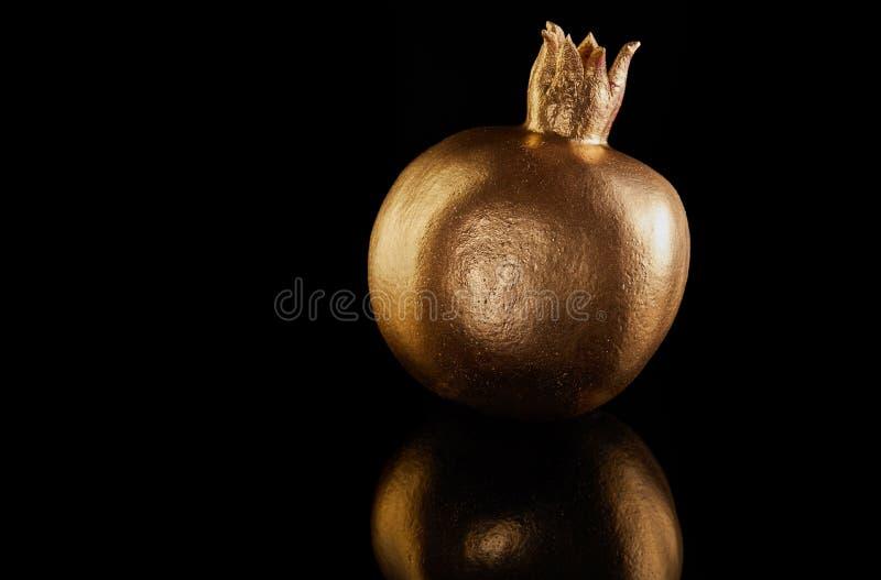 Rosh hashanah - jewish New Year holiday concept. Traditional symbols: golden pomegranate whole on a black background royalty free stock image