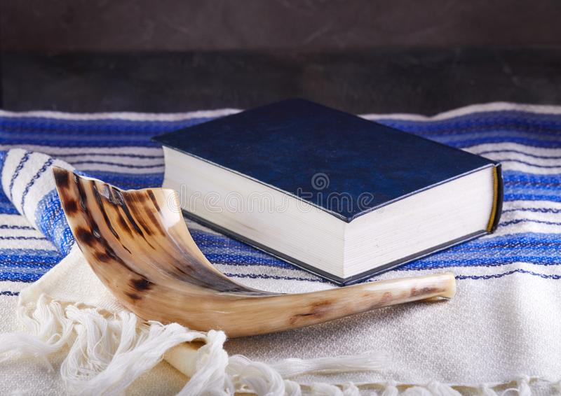 Rosh hashanah - jewish New Year holiday concept. Traditional symbols: Shofar - horn, tallite and Torah on a gray background stock photography