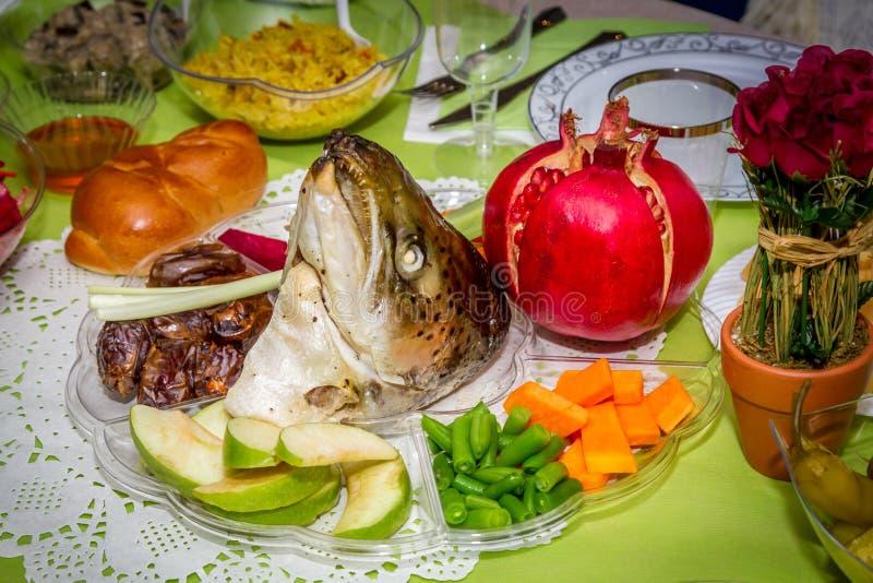 Rosh Hashanah, prato com a cabeça dos peixes, frutas e legumes imagens de stock