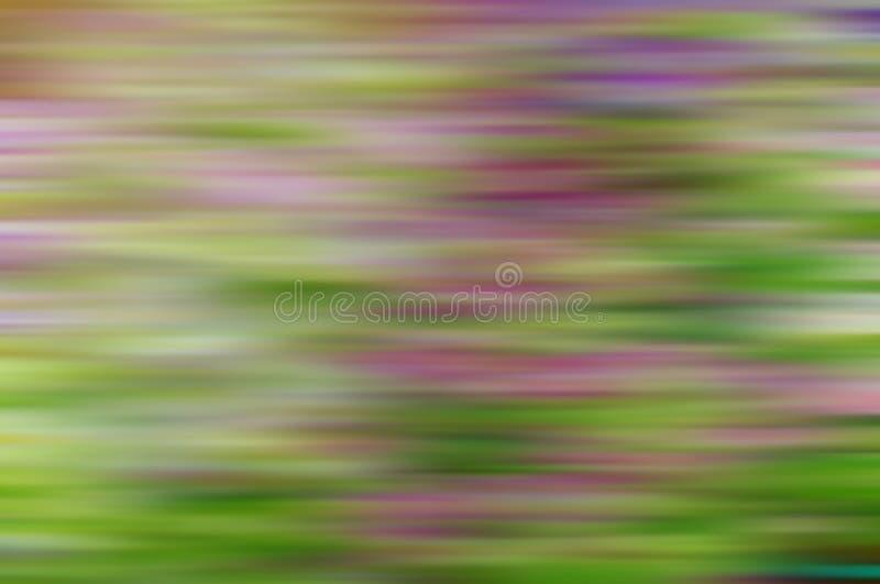 Rosiga och beigafläckar i ett grönt förtjust suddigt i horisontalriktning royaltyfria foton