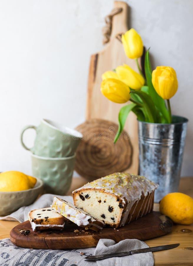 Rosinenkuchen auf einem hölzernen Brett mit Zitrone und gelben Tulpen lizenzfreie stockfotos