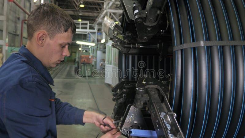 ROSJA, ANGARSK - CZERWIEC 8, 2018: Rolka threading zwitki drymbę Manufaktura plastikowe wodne drymby fabryczne Proces robić zdjęcie stock