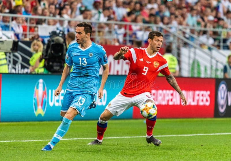 Rosja drużyna narodowa. strajkowicz Fedor Smolov przeciw San Marino drużyna narodowa. obrońcy Andrea Grandoni zdjęcie stock
