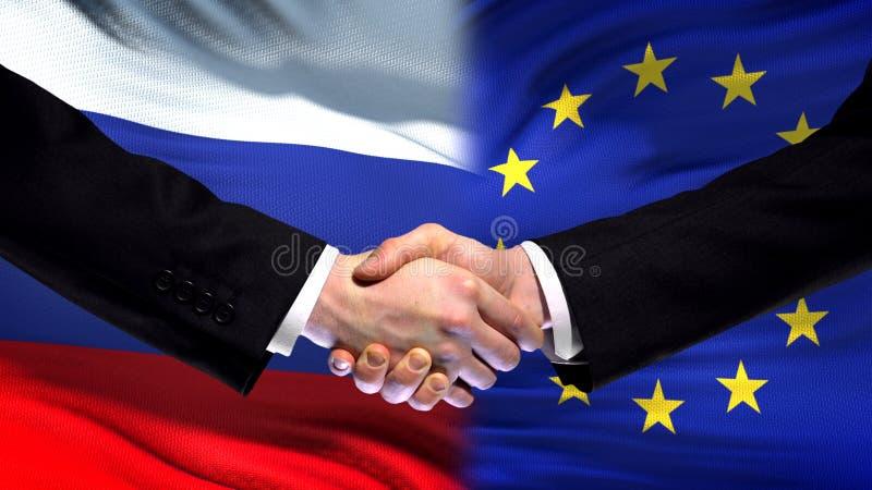 Rosja i Europejskiego zjednoczenia uścisk dłoni, międzynarodowa przyjaźń, chorągwiany tło obrazy royalty free