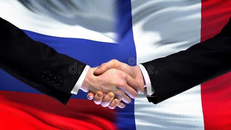 Rosja i Francja uścisk dłoni, międzynarodowy przyjaźń szczyt, chorągwiany tło zdjęcia royalty free