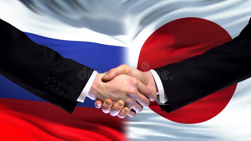 Rosja i Japonia uścisk dłoni, międzynarodowy przyjaźń szczyt, chorągwiany tło zdjęcia royalty free