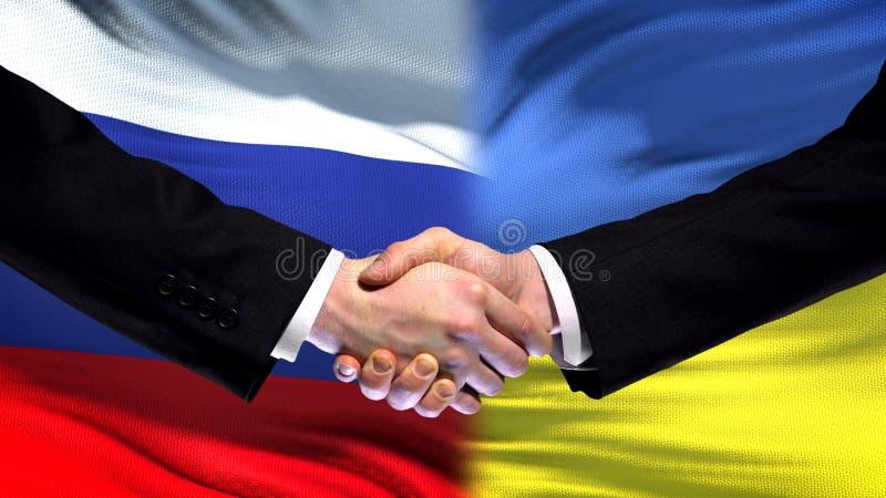 Rosja i Ukraina uścisk dłoni, międzynarodowy przyjaźń szczyt, chorągwiany tło zdjęcia royalty free
