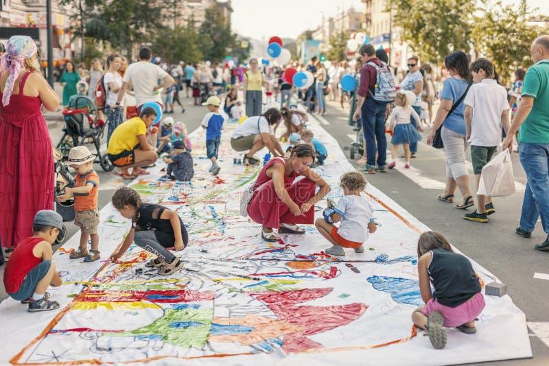 ROSJA Krasnoyarsk, Sierpień, - 25: Młode dzieci z rodzicami malują z kolorową kleistą taśmą na wielkiej rolce plastikowy sztandar zdjęcie royalty free