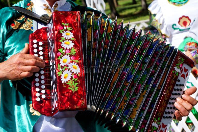 Rosja, Magnitogorsk, - Czerwiec, 15, 2019 Mężczyzna w obywatel odzieżowych sztukach akordeon - Tula harmonijka Parada na Sabantuy zdjęcia royalty free