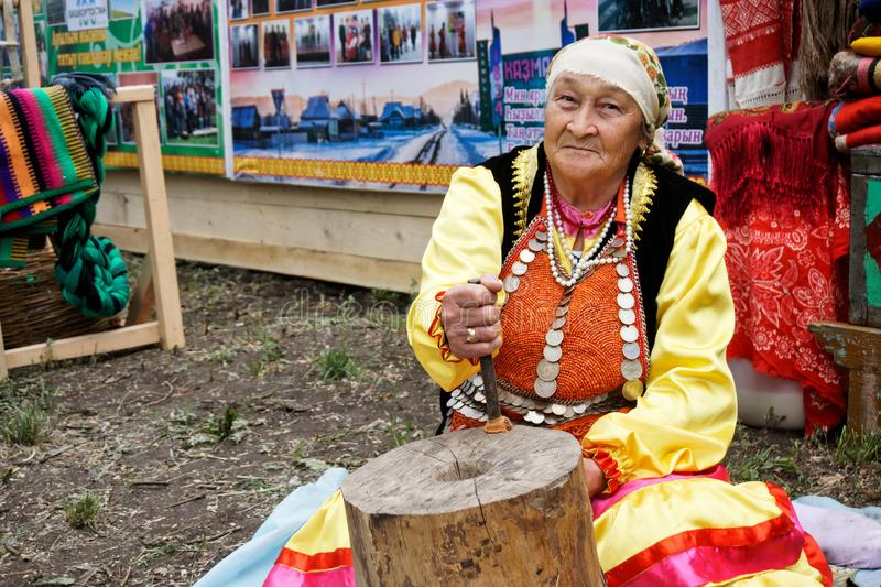 Rosja, Magnitogorsk, - Czerwiec, 15, 2019 Starsza kobieta demonstruje pracę stary drewniany ręczny millstone podczas zdjęcia stock