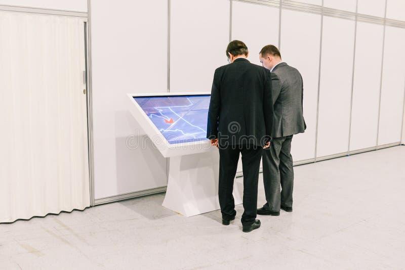 Rosja, miasto Moskwa, Grudzień - 18, 2017: Biznesmeni dyskutują biznesowego projekt blisko dotyka monitoru dw fotografia royalty free