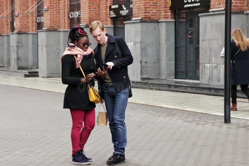03 29 2019 Rosja, Moskwa, młodzi ludzie spojrzenia przy informacją w telefonie na ulicie obraz stock