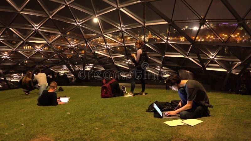 ROSJA MOSKWA, WRZESIEŃ, - 13, 2017 Młodzi ludzie z laptopu i pastylki pecetem przy Zaryadye parkiem pod futurystyczną szklaną kop zdjęcia royalty free