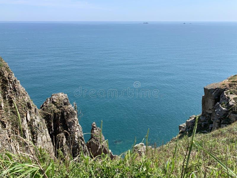 Rosja, Vladivostok Skalisty brzeg wyspa Shkot w archipelagu imperatorowa Eugenie w pogodnym letnim dniu fotografia royalty free