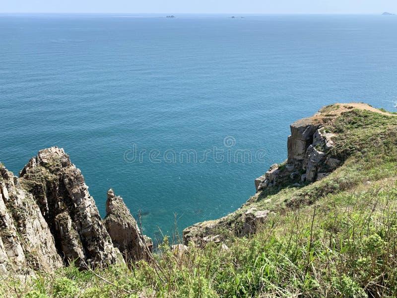 Rosja, Vladivostok Skalisty brzeg wyspa Shkot w archipelagu imperatorowa Eugenie w pogodnym letnim dniu obrazy stock