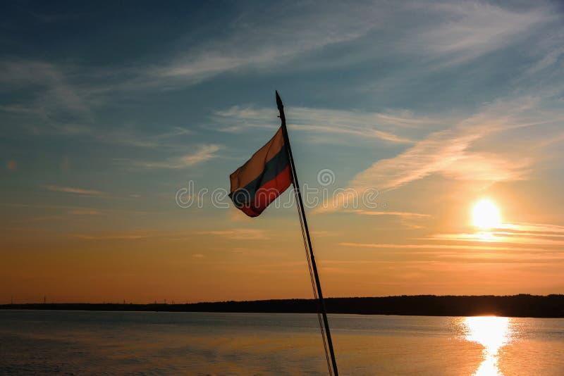 Rosjanin flaga lata na flagpole przy zmierzchem przeciw tłu niebo i rzeka zdjęcie stock