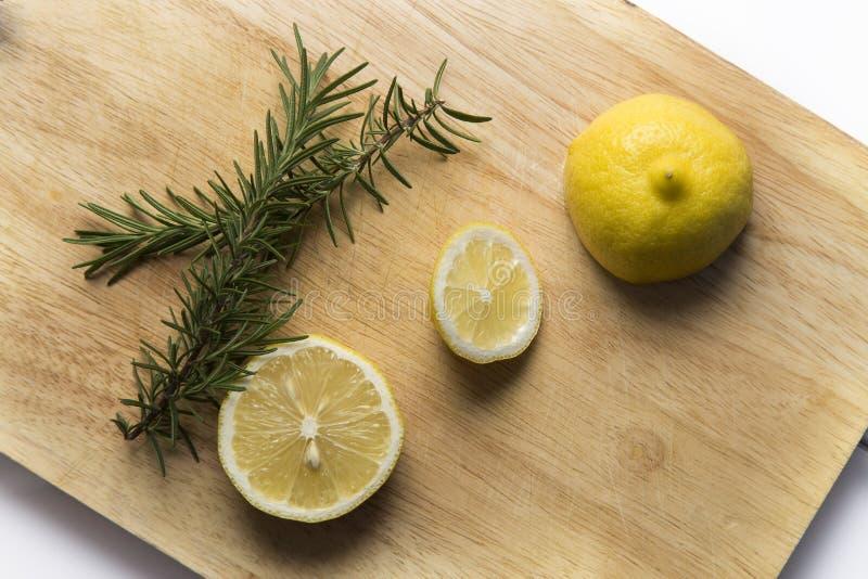 Rosmarini e limone sul blocchetto di spezzettamento immagini stock