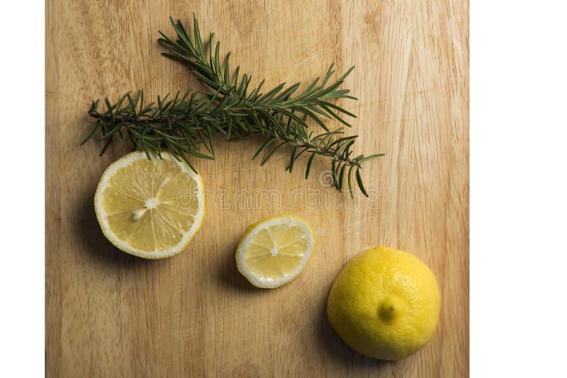 Rosmarini e limone sul blocchetto di spezzettamento fotografia stock