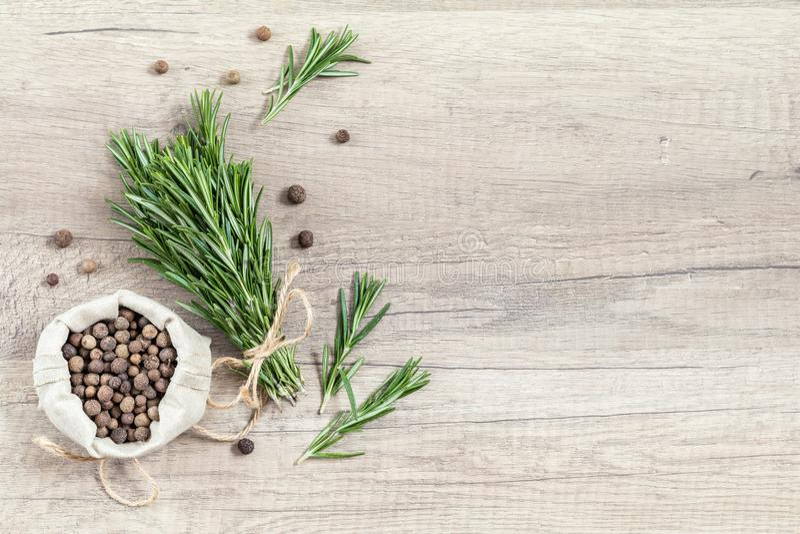 Rosmarini e pepe fragrante su superficie di legno leggera immagini stock libere da diritti