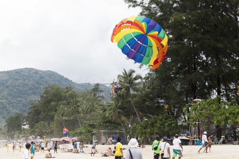 Rosnący w niebo wielkim spadochronie w niebieskie niebo tropikalnej plaży Dwa Chińskiego turysty lata na spadochronie nad morzem  obraz royalty free