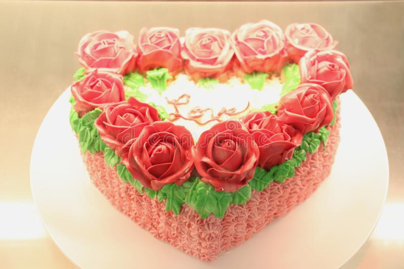 Rosor dekorerade överst den hjärta formade kakan med ord av förälskelse royaltyfri foto