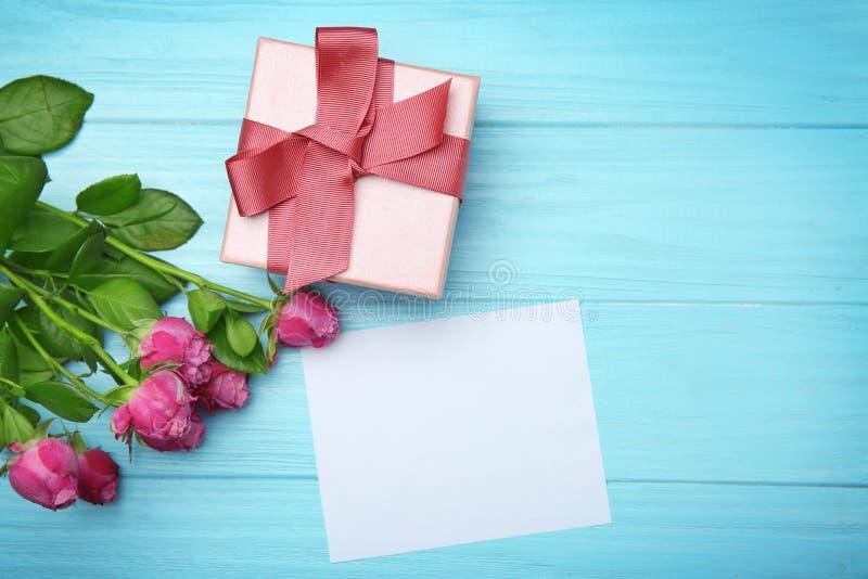 Rosor, gåvaask och tomt kort på träbakgrund royaltyfri bild