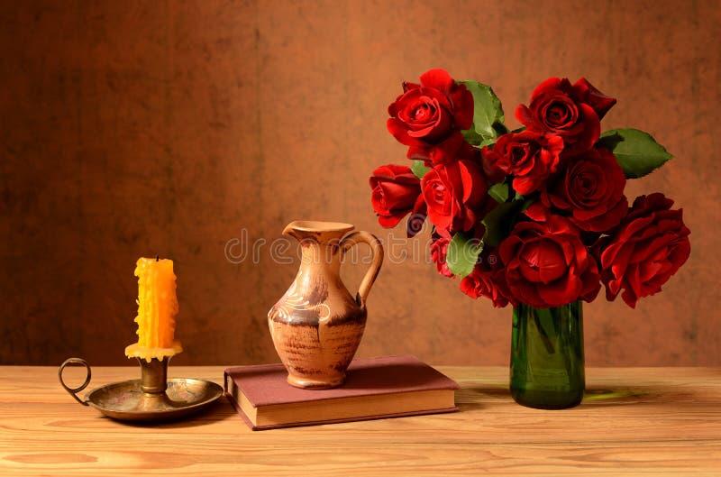 Rosor i en vas, böcker och stearinljus royaltyfri fotografi