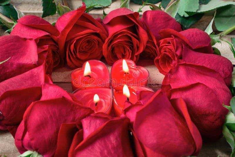 Rosor läggas ut i formen av en hjärta på en träbakgrund, bland dem bränner hjärta-formade stearinljus royaltyfria foton