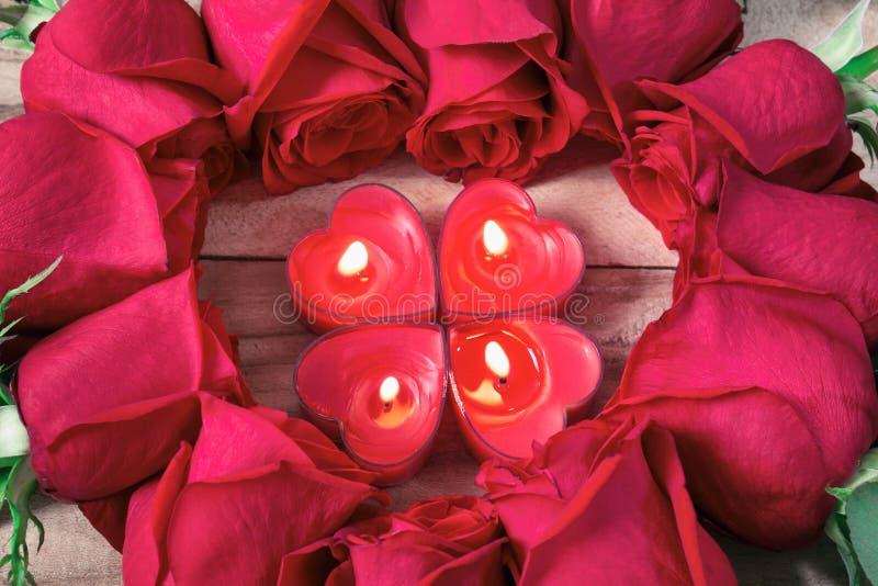 Rosor läggas ut i formen av en hjärta på en träbakgrund, bland dem bränner hjärta-formade stearinljus royaltyfri bild