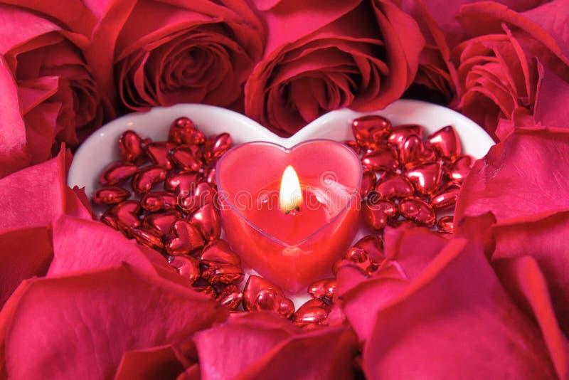 Rosor läggas ut i formen av en hjärta på en träbakgrund, bland dem en platta i formen av en hjärta och en stearinljus på den fotografering för bildbyråer