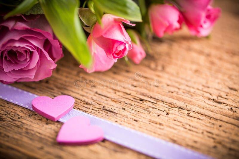 Rosor med hjärtor på träjordning royaltyfri fotografi