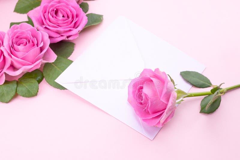 Rosor och kuvert p? en ljus bakgrund Bukett och bokstav som en g?va i begreppet av valentin dag och kvinnors dag fritt arkivbilder