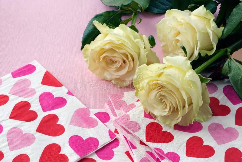 Rosor och servetter med röda hjärtor fotografering för bildbyråer