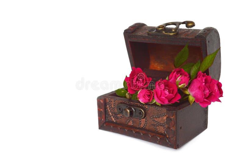 Rosor som är ordnade i skattbröstkorg arkivfoto