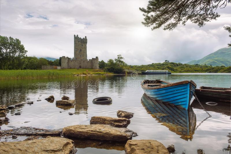 Ross Castle ruins in Ireland. Ross Castle ruins and the Lough Leane lake with a blue boat in the foreground in the Killarney National Park, Ireland stock photo