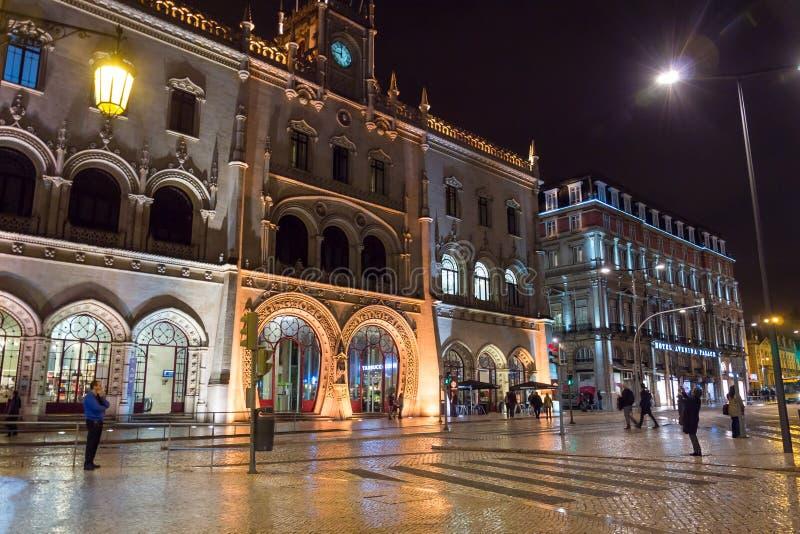 Rossio järnvägsstationingång på natten, folk som är främst av den neo-Manueline stilfasaden av den Rossio järnvägsstationen i Lis royaltyfri foto