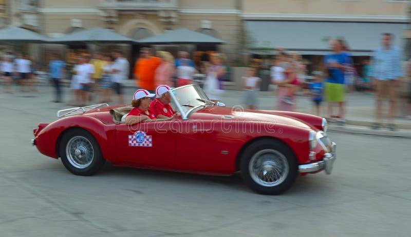 Rosso classico MGA che è guidato tramite la piazza in Rovigno nel giro della Croazia fotografie stock libere da diritti