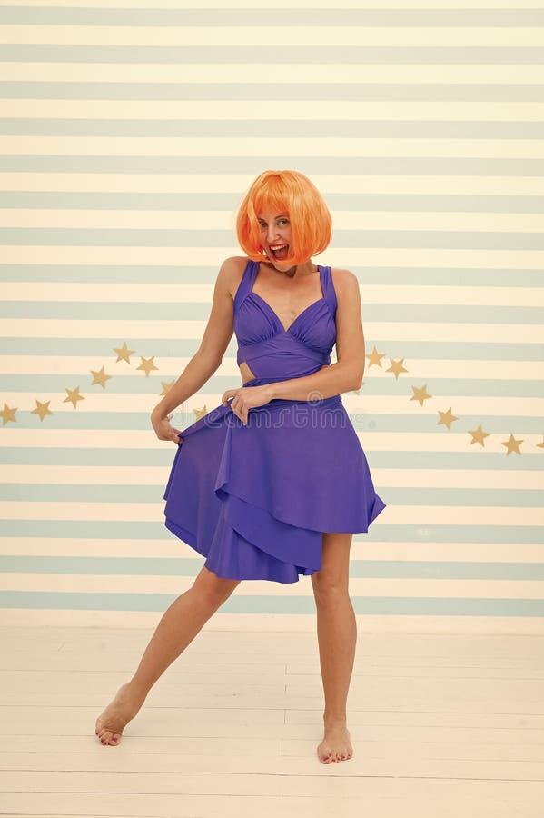 Rosso di signora o parrucca dello zenzero che posa in vestito blu Concetto comico ed umoristico Divertiresi allegro di umore dell fotografia stock libera da diritti