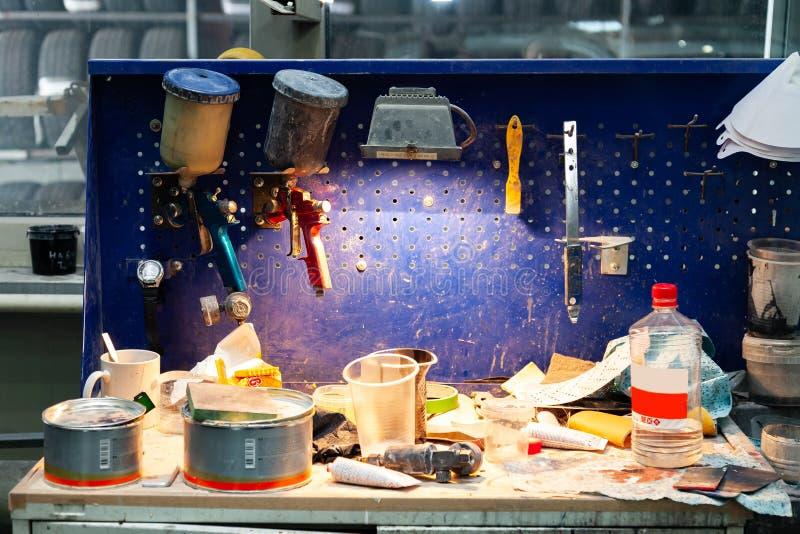 Rosso e blu dello spruzzatore della pistola della vernice di carrozzeria due installati su un banco da lavoro in un'officina di r immagine stock