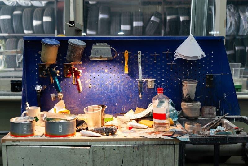 Rosso e blu dello spruzzatore della pistola della vernice di carrozzeria due installati su un banco da lavoro in un'officina di r fotografia stock