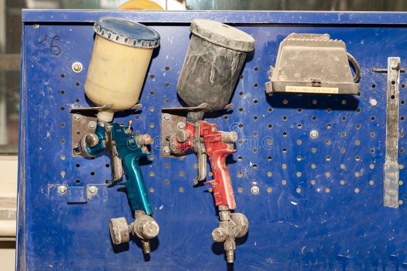 Rosso e blu dello spruzzatore della pistola della vernice di carrozzeria due installati su un banco da lavoro in un'officina di r immagini stock