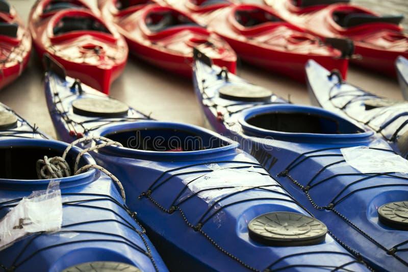 Rosso e canoe colorate blu parcheggiati fotografie stock