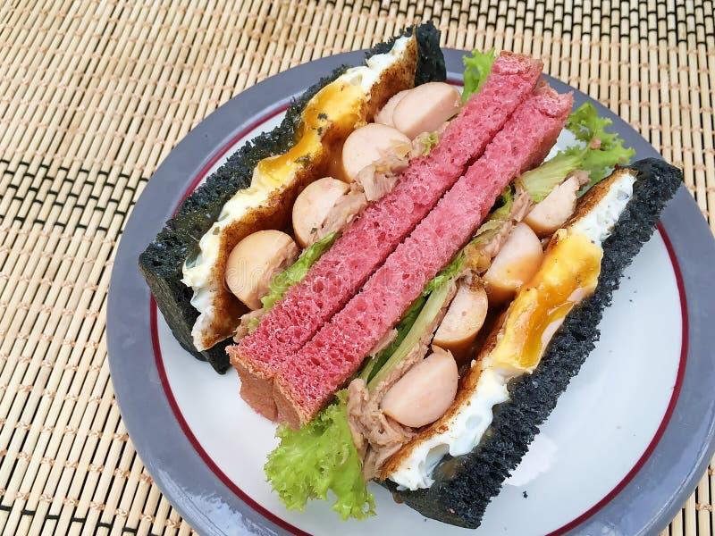 Rosso e nero con il panino dell'uovo fritto e della salsiccia immagine stock libera da diritti