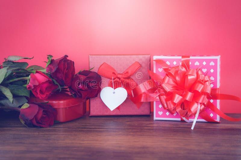 Rosso e rosa del contenitore di regalo di giorno di biglietti di S. Valentino sul fiore di legno della rosa rossa giorno di bigli immagini stock libere da diritti