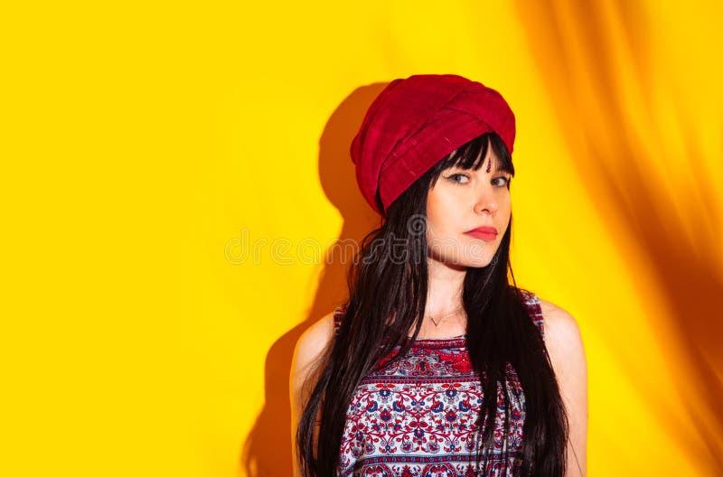 Rosso indiano del turbante della luce del sole dell'ombra del fondo giallo dello studio del ritratto della donna immagini stock libere da diritti