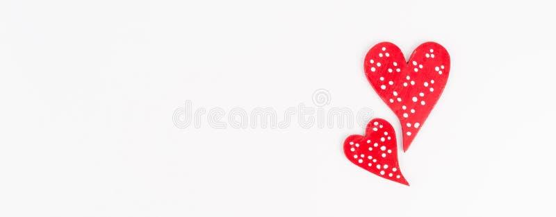 Rosso sente, due cuori rossi punteggiati bianchi isolati su fondo bianco, festa romantica, fotografia stock